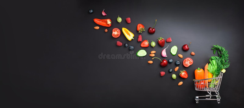 Shoppingspårvagn som fylls med nya organiska grönsaker, frukter och bär på den svarta svart tavlan Top beskådar vegetarian royaltyfri bild