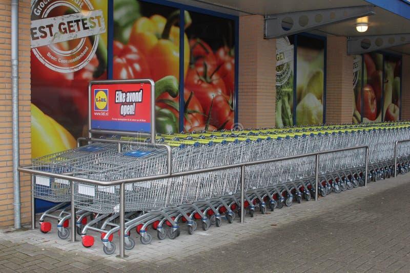 Shoppingspårvagnar på den Lidl supermarket arkivfoto