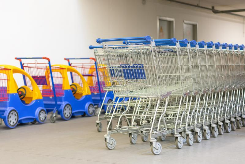 Shoppingspårvagnar - supermarketshoppingtema Rad av shoppingvagnar med blåtthandtag och barns vagnar stock illustrationer