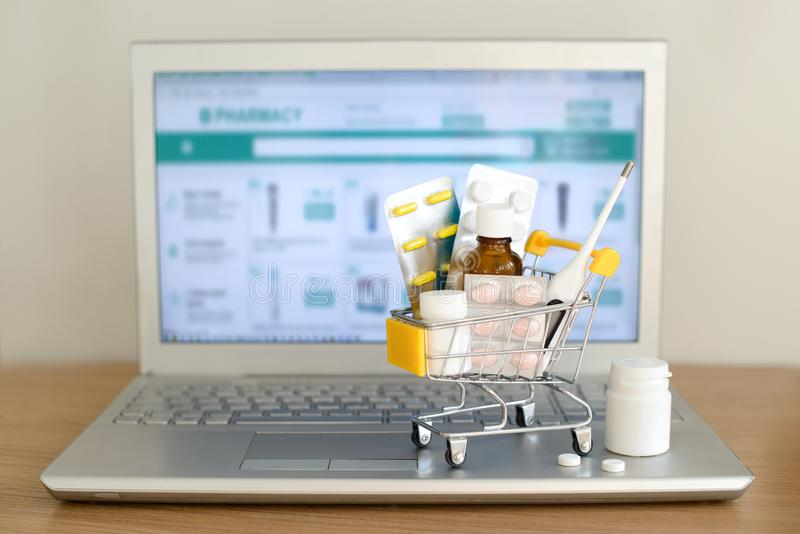 Shoppingvagn att leka med medikament framme av bärbar datorskärmen med apotekwebbplatsen på den Piller blåsapackar, medicinska fl arkivfoton
