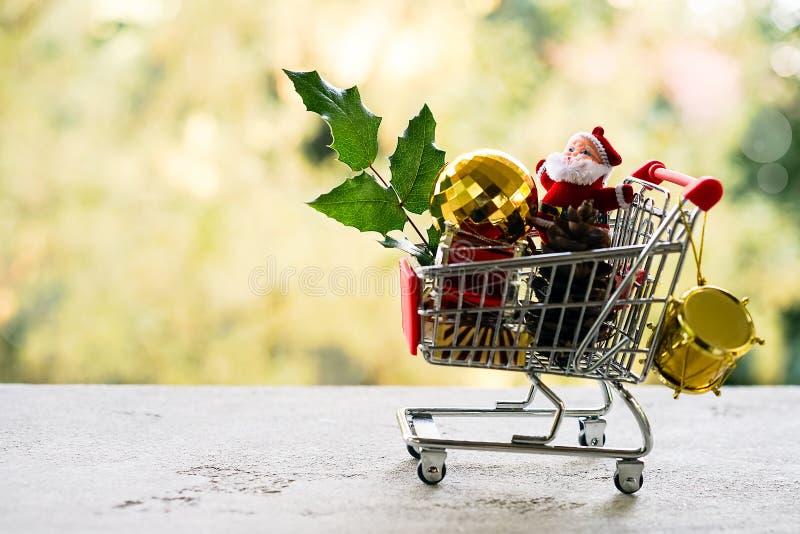 Shoppingvagn med gåvan eller gåva och mistel, järnekblad på bokeheffektbakgrund Jul och försäljningsbegrepp för nytt år royaltyfri fotografi