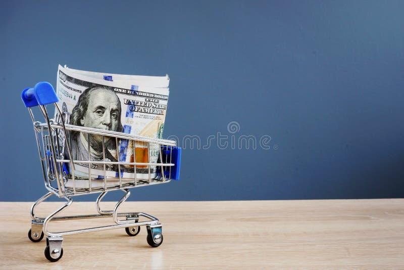 Shoppingvagn med pengar Ögonblickliga kassalån arkivfoton
