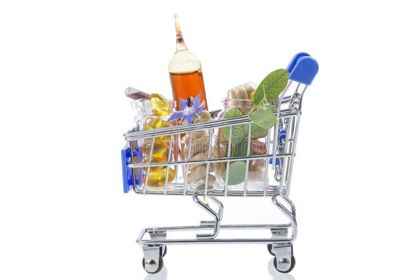 Shoppingvagn mycket av den farmaceutiska drogen, medicinpreventivpillerar, växter och mattillägget arkivbild