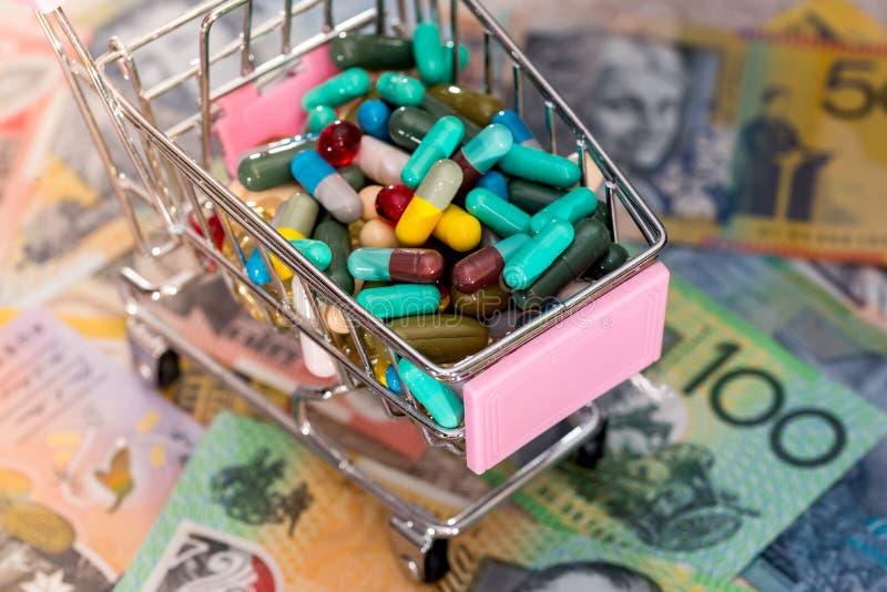 Shoppingvagn mycket av färgglade piller på australiska dollar royaltyfri bild
