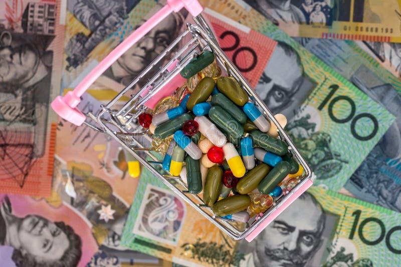 Shoppingvagn mycket av f?rgglade piller p? australiska dollar arkivfoto