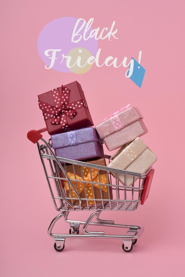 Shoppingvagn mycket av gåvor och text svarta fredag arkivfoto