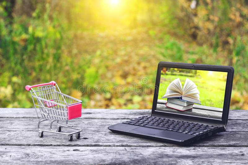 Shoppingvagn och bärbar dator med böcker på skärmen på den gamla trätabellen på naturbakgrunden Dra tillbaka till skolan, utbildn arkivbilder