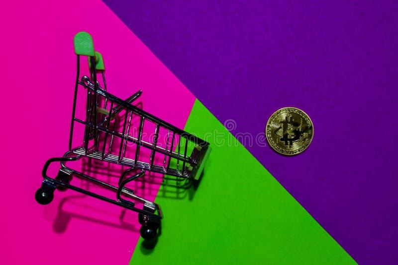Shoppingvagn och Bitcoin guld på rosa, purpurfärgad och grön färgrik bakgrund fotografering för bildbyråer