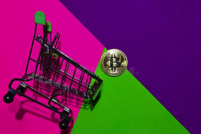 Shoppingvagn och Bitcoin guld på rosa, purpurfärgad och grön färgrik bakgrund royaltyfria foton