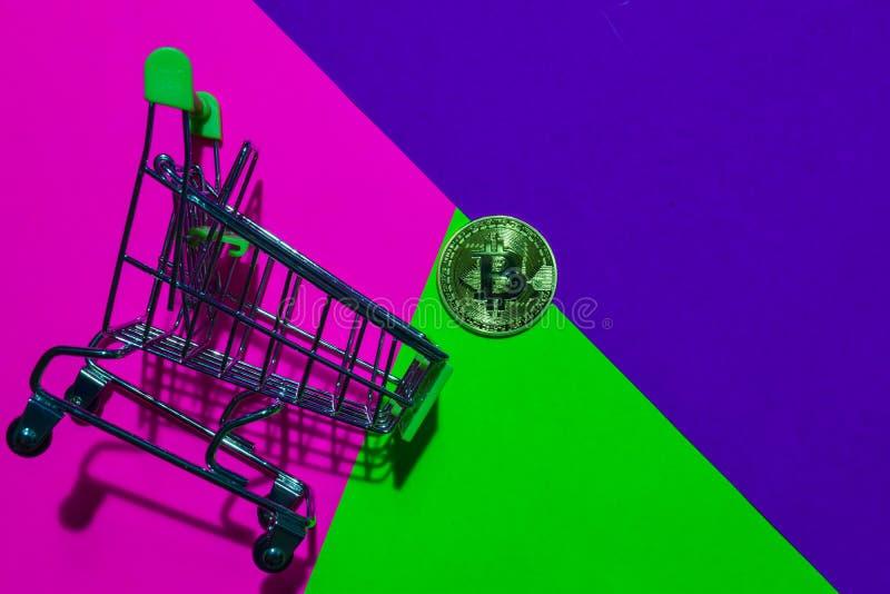 Shoppingvagn och Bitcoin guld på rosa, purpurfärgad och grön färgrik bakgrund arkivbilder