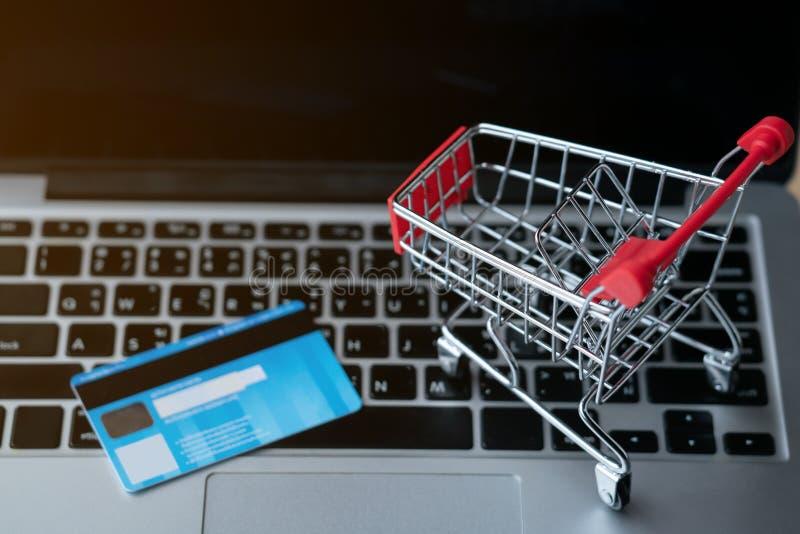 Shoppingvagn och craditkort på bärbara datorn arkivfoton