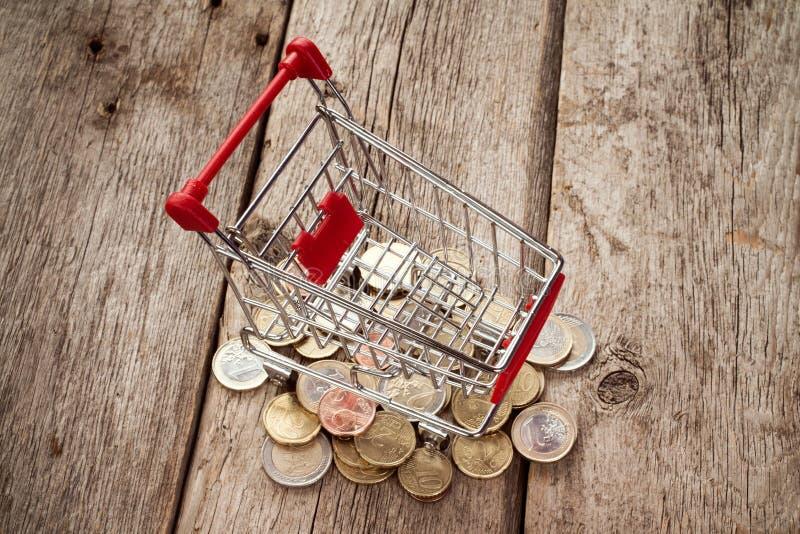 Shoppingvagn på högen av euromynt arkivfoton