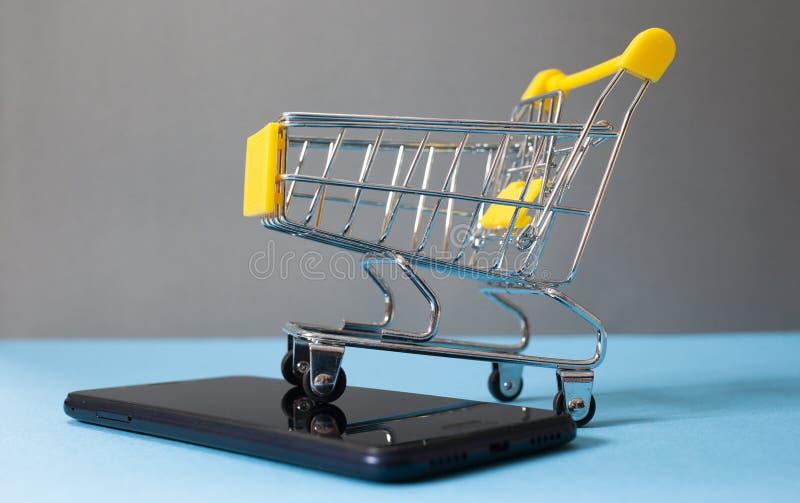 shoppingvagn på smartphonen - e-kommers royaltyfria bilder