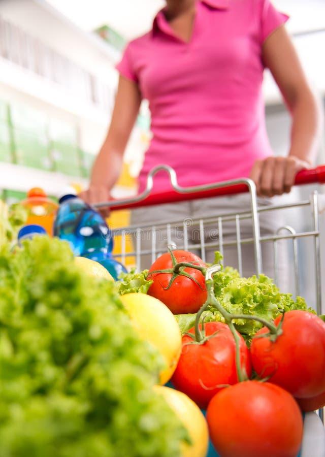 Shoppingvagn som fylls med grönsaker och frukt arkivbilder