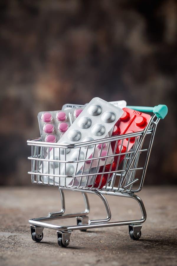 Shoppingvagn som fylls med preventivpillerar royaltyfri foto