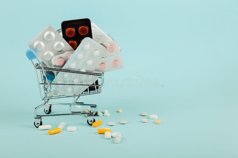 Shoppingvagn som laddas med piller på en blå bakgrund Begreppet av medicin och försäljningen av droger kopiera avstånd royaltyfri bild