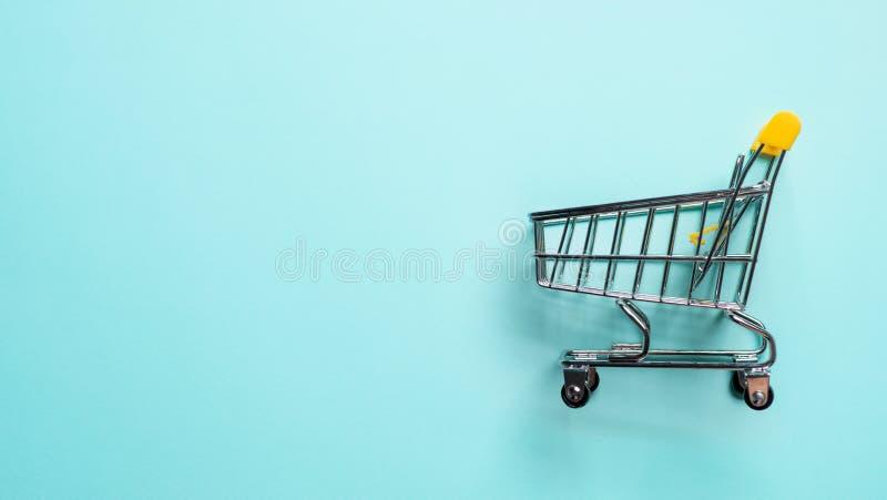 Shoppingvagn som vacklas på blått, kopieringsutrymme royaltyfria bilder