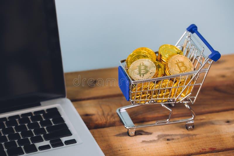 Shoppingvagnen fyllde med högar av cryptocurrencybitcoinmynt med datorbärbara datorn som var närliggande på träplattformen arkivfoton