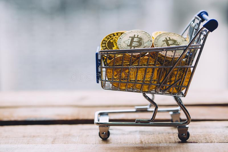 Shoppingvagnen fyllde med högar av cryptocurrencybitcoinmynt på träplattformen arkivfoto