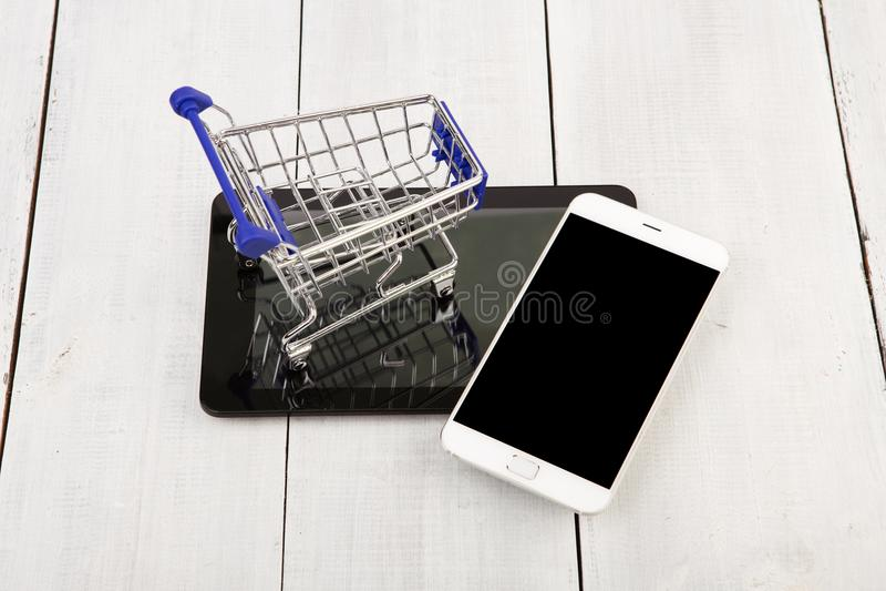 Shoppingvagnen på minnestavlaPC:n nära till smartphonen på en vit uppvaktar arkivfoto