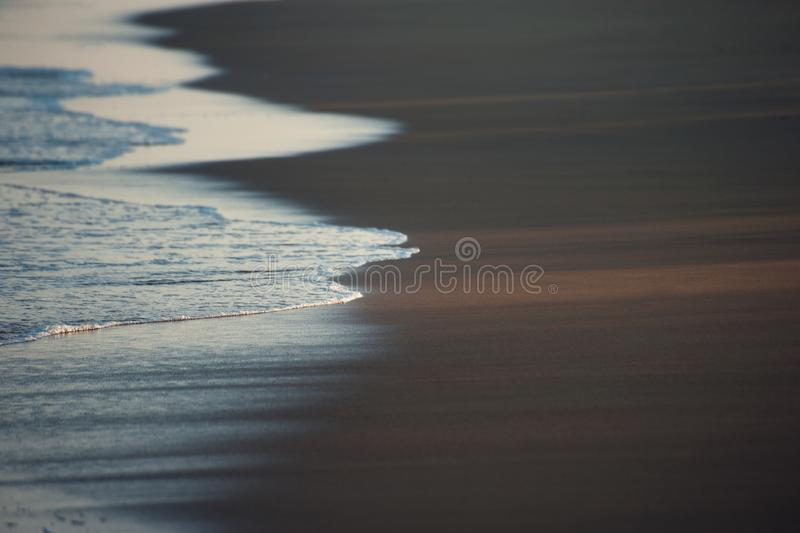 Shore of the Indian ocean. Sand and water. Ocean shore. Water on the sand on the summer  beach.Evening sunset on the beach stock photography