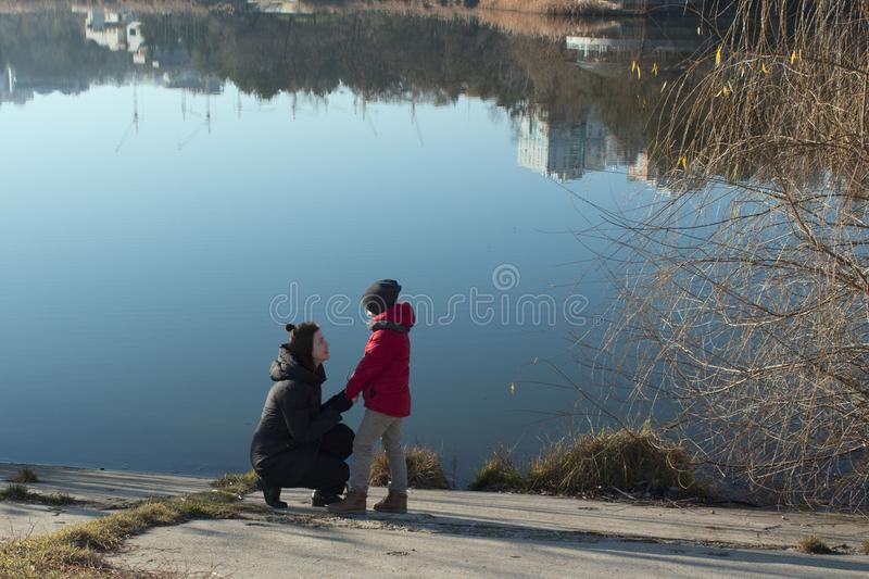 Mother with son walking near lake royalty free stock photos