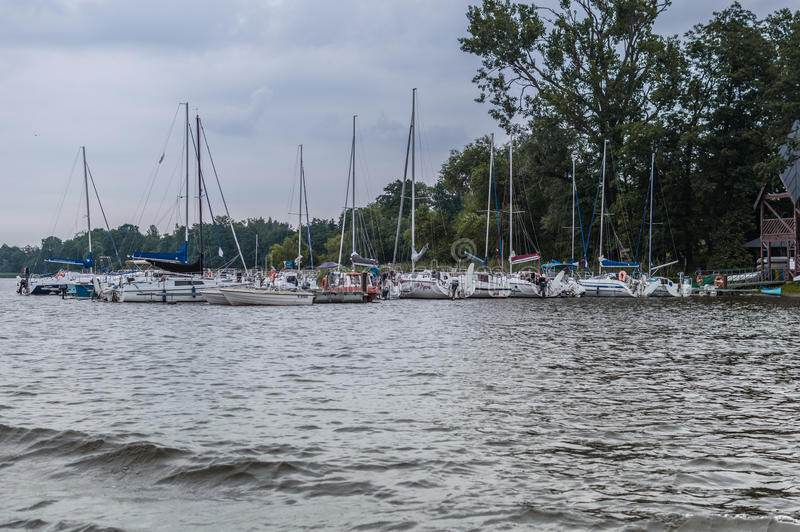 Shore of lake in Poland, near city Ilawa. Yachts and other boats moored at marina.  stock images