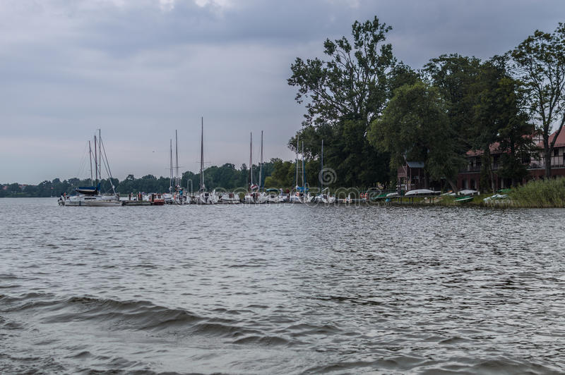 Shore of lake in Poland, near city Ilawa. Yachts and other boats moored at marina.  royalty free stock photo
