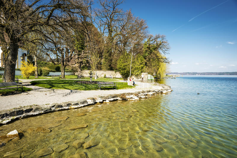 Shore of Lake Starnberg in Germany. With gravel, trees, benches and people in sunny weather royalty free stock images