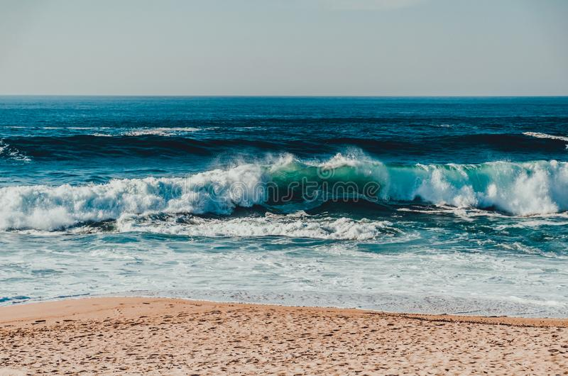A shore of the sea or ocean with sand and big waves with foam at the sunny weather stock image