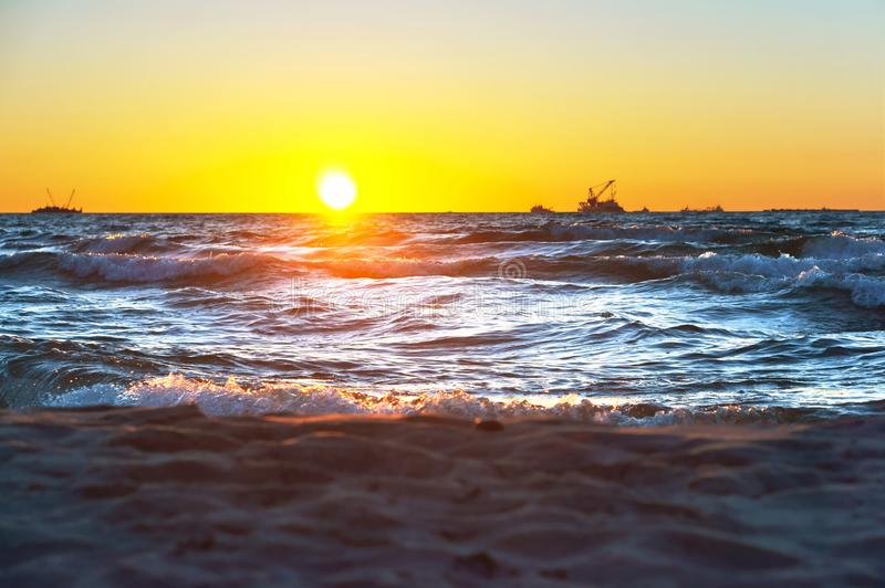Red yellow sunset on the sea, shore in the surf of the waves of the Baltic sea and a magnificent sunrise. Shore in the surf of the waves of the Baltic sea and a royalty free stock photography