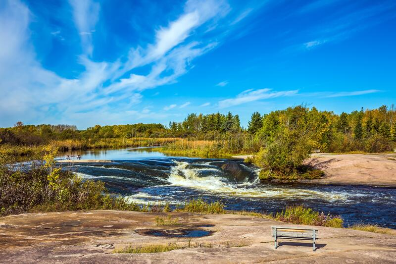 On the shore is a wooden bench. Waterfall drain on the smooth stones of the Winnipeg River. On the shore is a wooden bench for tourists. The concept of royalty free stock images