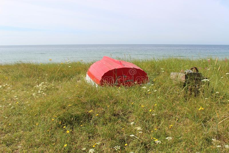 "On the shore of Ystad, South Sweden, Scandinavia, Europe. Boat in the grass, in front of the Baltic sea. Ystad is film location of the crime series "" royalty free stock photography"