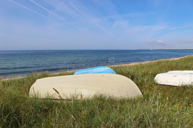 "On the shore of Ystad, South Sweden, Scandinavia, Europe. Boats in the grass, in front of the Baltic sea. Ystad is film location of the crime series "" royalty free stock photo"