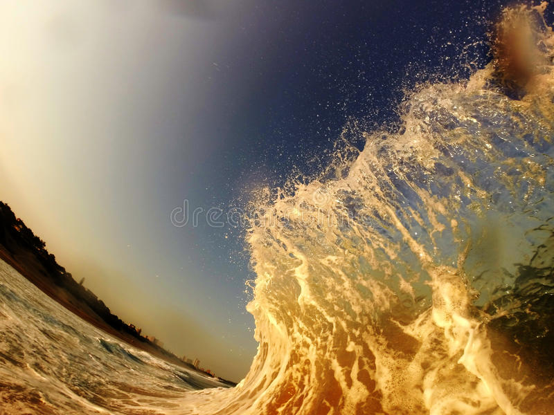 Shorebreak. Wave breaking catching the sunset glow stock images
