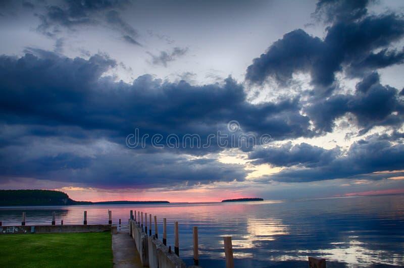 Shoreline e di cielo ripieno di nuvola in Ephraim, WI al tramonto fotografie stock