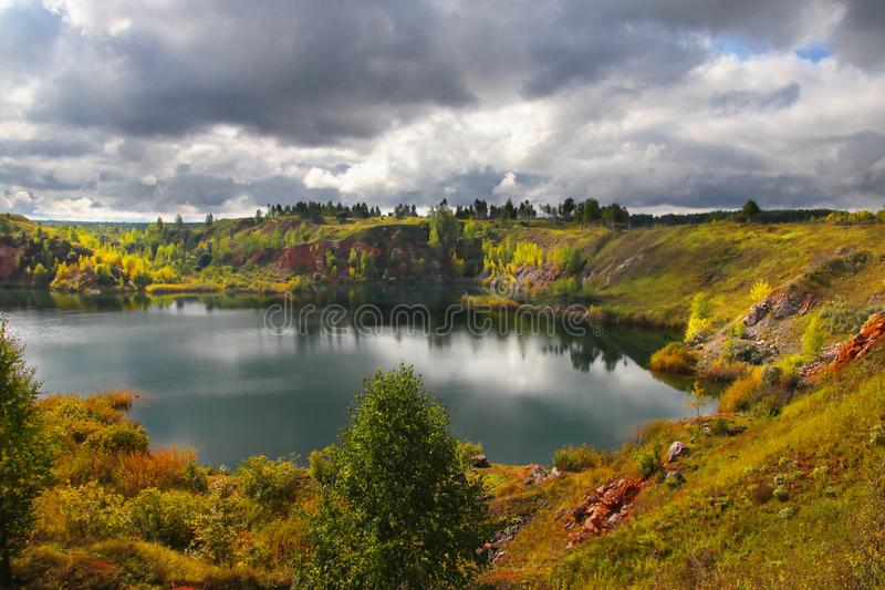 The shores of an abandoned quarry are illuminated by the rays of the sun on a cloudy day through heavy autumn clouds. View from the cliff to an abandoned quarry royalty free stock image