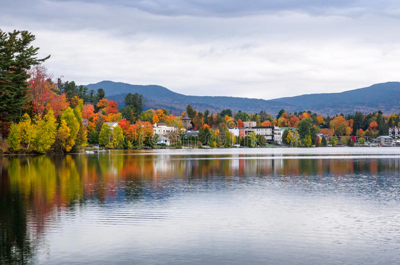 The Shores of Mirror Lake in Lake Placid, NY, on a Cloudy Autumn Day. With Buildings among Colourful Trees Reflecting in Calm Waters royalty free stock image