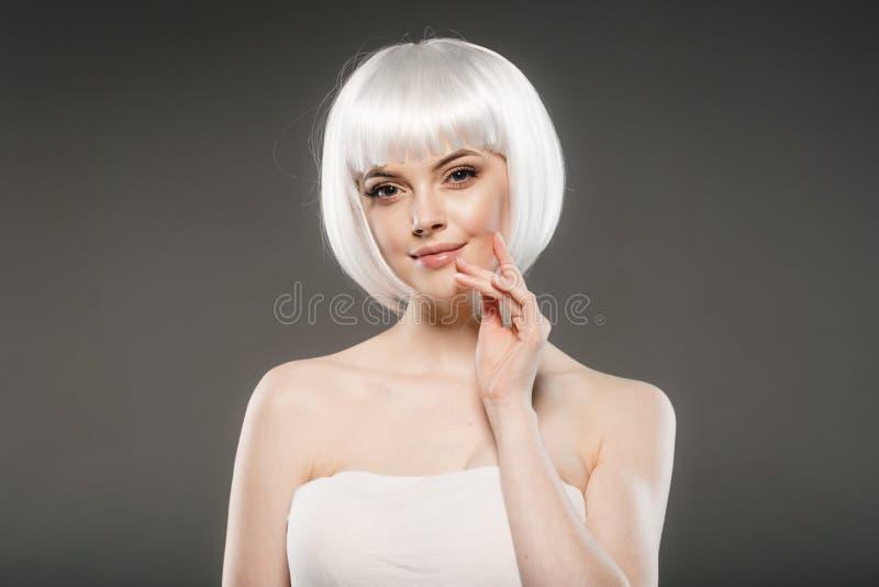 Short blonde hair woman bob platinum hairstyle. Studio shot stock image