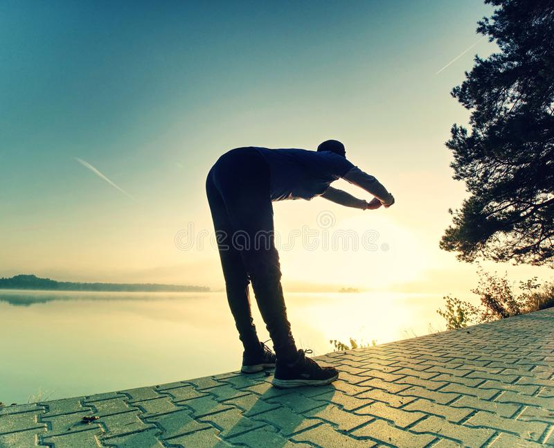 Short break for breath. Silhouette of active man on lake beach. Short break for breath. Silhouette of active man exercising and stretching on the lake beach at stock image