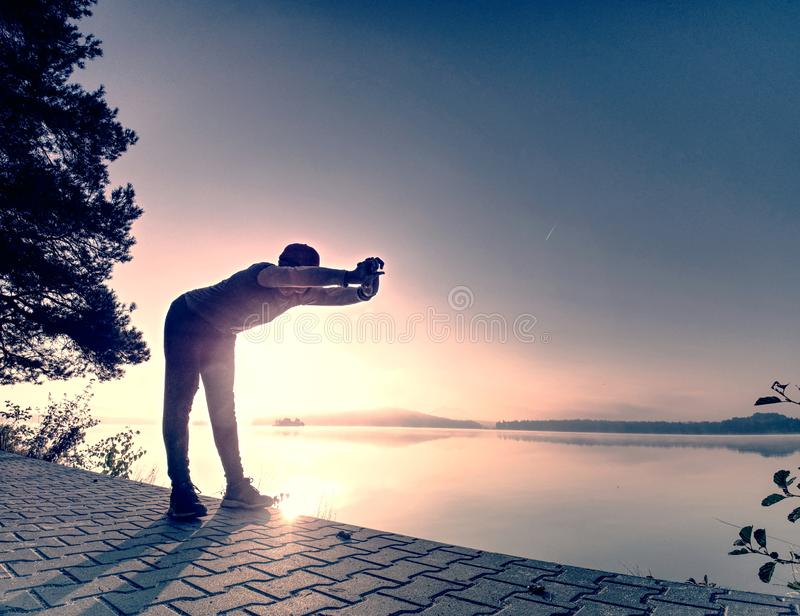 Short break for breath. Silhouette of active man on lake beach. Short break for breath. Silhouette of active man exercising and stretching on the lake beach at royalty free stock image