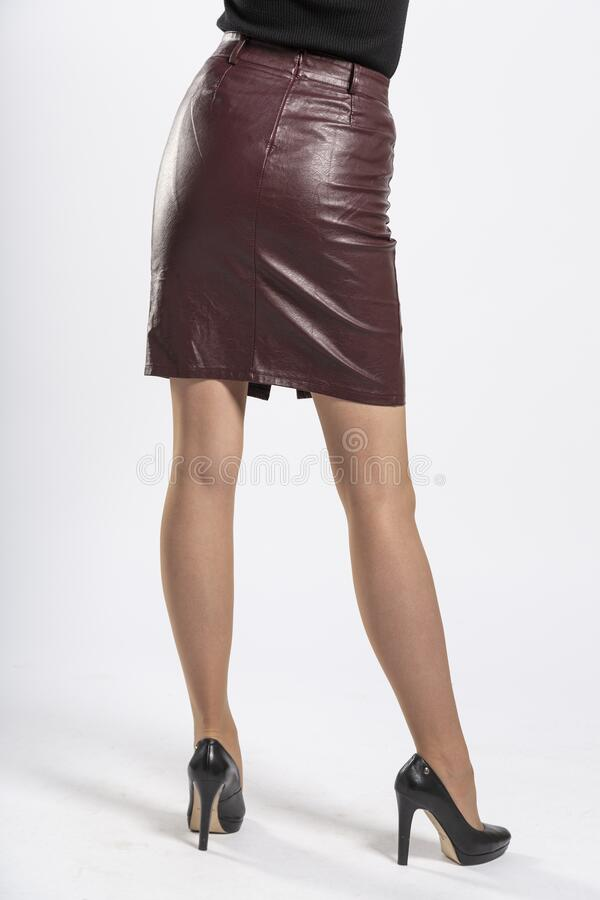Short brown leather skirt with a leather belt close-up, women`s feet with black high-heeled shoes on a white background. A girl in a short leather skirt stock images