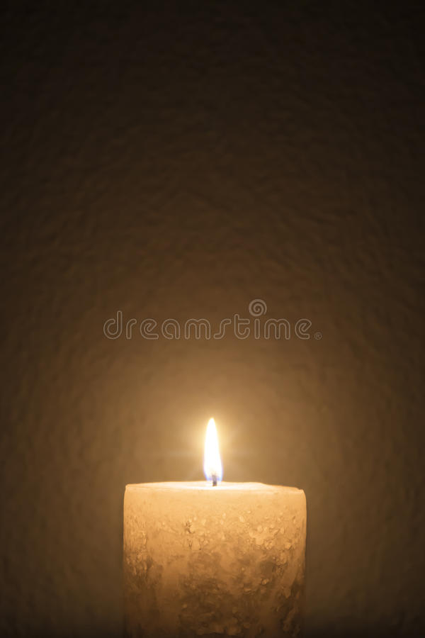 A short candle burns brightly in dark room stock image