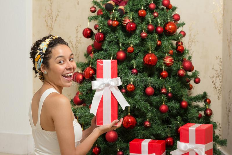 Black woman is happy with her Christmas present. Ornate tree and royalty free stock photography