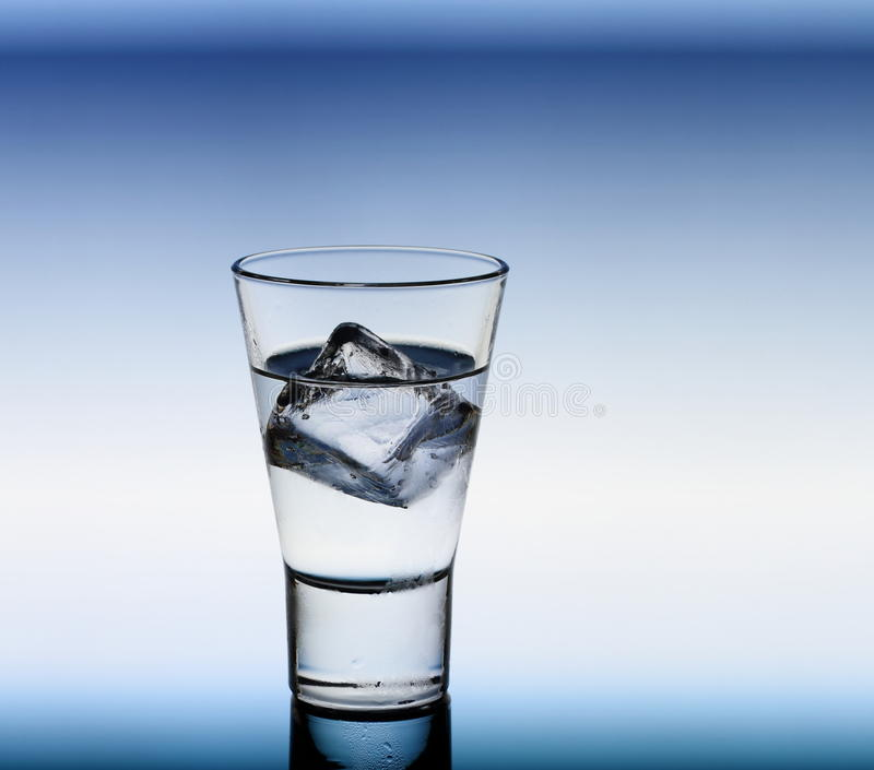 Short drink glass with clear liquid and ice cubes. Blue background royalty free stock photos
