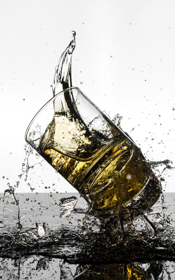 Spectacular High Speed shot of whiskey Glasees breaking. A short glass was dropped onto another one full of whiskey, and a picture was taken while they were mid royalty free stock images