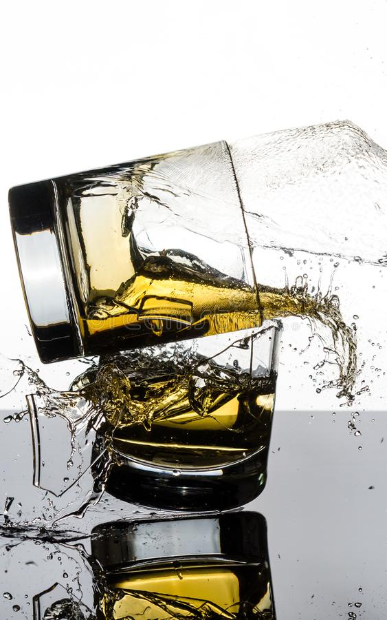 Spectacular High Speed shot of whiskey Glasees breaking. A short glass was dropped onto another one full of whiskey, and a picture was taken while they were mid royalty free stock photography