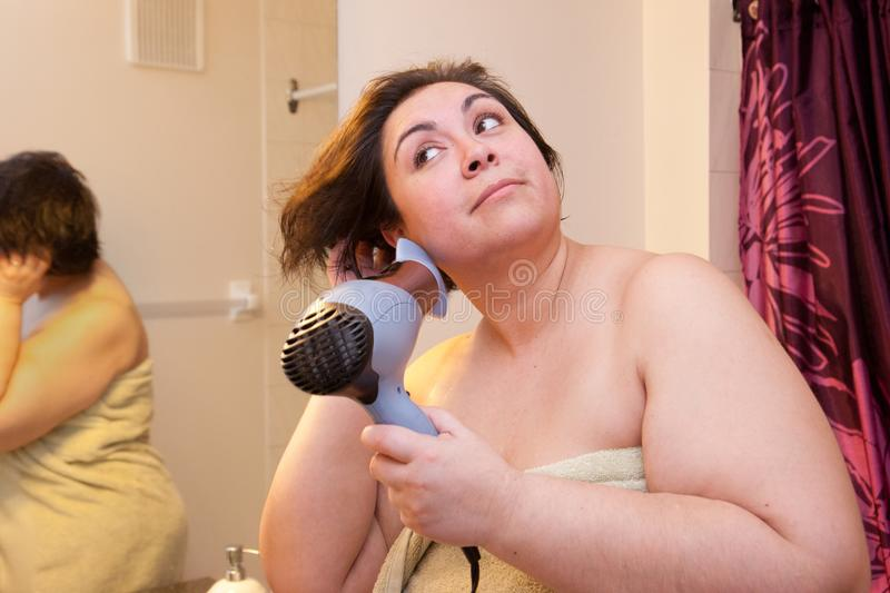 Short hair don`t care. Beautiful woman flips her short hair while using a hairdryer, eyes smiling in the morning stock images