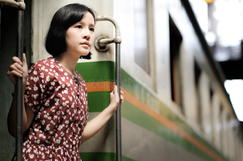 Beautiful girl traveling by train. Short-haired Asian woman wearing a red floral dress is traveling with a vintage train beautiful journey girl passenger royalty free stock photo