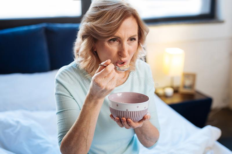 Short-haired fit mature lady carrying metal spoon and tasting breakfast. Eating morning porridge. Short-haired fit mature lady carrying metal spoon and tasting royalty free stock images